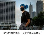 Small photo of young female wearing medical mask in modern city street, stylish trendy girl with blue hair wearing fashionable protective medical mask amid coronavirus fears, covid19 pandemic, new fashion concept