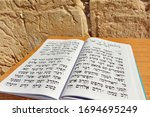 Small photo of JERUSALEM-NOV 05 2010:King David Book of Psalms in Hebrew against the Wailing Wall. The Messiah will be a patrilineal descendant of King David, and will gather the Jews back into the Land of Israel.