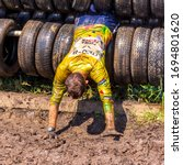 Small photo of Russia, Samara, June 2019: athletic youth participates in a race of heroes and overcomes obstacles car tires on a summer day in the village of Roshchinsky . Text in Russian: race of heroes, platoon