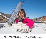 A lady motorhome owner cleans the roof of her vehicle.The top half of her body is visible as she has climbed through the roof skylight.Vivid pink fleece.Amusing.Image - stock photo