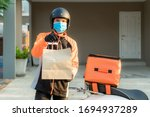 Small photo of Delivery Asian man wear protective mask in orange uniform and ready to send delivering Food bag in front of customer houes with case box on scooter, express food delivery and shopping online concept.
