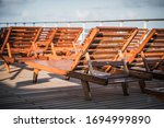 Cruise Ship Empty Deck and Wooden Deckchairs Closeup. Travel Crises Theme. - stock photo