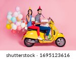 Small photo of Full body profile side photo funny two people friends drive chopper deliver gift boxes whistle blower air baloons fly wear birthday cones shirt pants dotted retro red isolated pink color background
