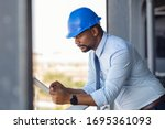 Mature manager using digital tablet on construction site. Serious african engineer checking email at building site wearing blue hardhat. Architect working on digital tablet leaning at balustrade. - stock photo