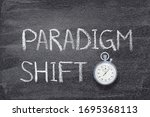 Small photo of paradigm shift phrase written on chalkboard with vintage precise stopwatch