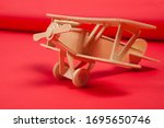 Wooden toy airplane biplane on a red background. Handmade work. For military holidays - February 23, defender of the Fatherland Day, may 9, Victory Day. To avoid war. 1945 victory.