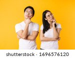 Small photo of Image of serious multinational man and woman thinking and looking aside isolated over yellow background