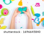 Small photo of Little girl hands close up playing with colorful modeling clay on white background. Home Education game with clay. Child sculpting heart figure from clay. Top view. Early development concept