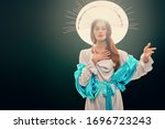 Small photo of The Virgin Mary portrait on a dark background with nimbus in rays of light. Modern art in religion.