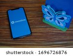 Small photo of Madrid, Spain - April 07, 2020; Mention Apple Apps on Iphone Screen with Blue Butterfly Tissue Holder on a Wooden Table. Mention is a social media tool. #Mention