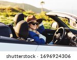 Outdoors lifestyle fashion portrait of stunning young woman driving cabriolet. Happy girl smiling, holding hat. Wearing stylish jeans coat, hat, sunglasses. Woman driving. Travel by car. Close up - stock photo