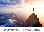Small photo of Adventure, Explore and Lifestyle Concept Composite. Adventurous Man Hiker With Hands Up on top of a Steep Rocky Cliff. Sunset or Sunrise. Landscape Taken from Washington, USA.