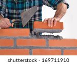Small photo of Constructor hand holding a brick and building a wall.