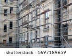 Small photo of Tall building under construction with scaffolds. Scaffold. Construction Scaffoldings