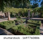Garden and courtyard Patio de los Surtidores with central fountain and red flowers in Alcazaba Fortress Malaga Spain.
