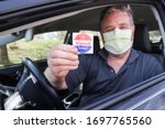 """Small photo of Man holding an """"I voted today"""" sticker after voting wearing a face mask to prevent the spread of coronavirus"""