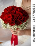 Bride Holding Red Rose Bouquet...