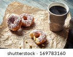 Closeup of hot coffee and donuts on paper - stock photo