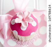 Small photo of Cupcake decorated with a pink fondant flower