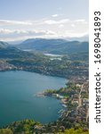 Top view of the city of Lugano, Switzerland from the height of Mount Monte Bre. Beautiful mountain scenery on a sunny summer day. View of Lake Lugano and the Alpine mountains.