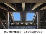 Small photo of Replacing 2 plastic skylight windows with new one in mansard garret,or attic,of old private residential house.Installing windows.Roofer and window master work.Wooden load-bearing beams.Selective focus
