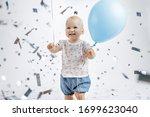 Small photo of A little cute happy girl rejoices and laughs on her first birthday on a white background. Slapstick with confetti, a balloon filled with helium, a silver cap.