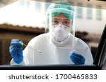 Small photo of Doctor or nurse wearing PPE, N95 mask, face shield and personal protective gown standing beside the car/road screening for Covid-19 virus