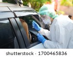 Small photo of Doctor or nurse wearing PPE, N95 mask, face shield and personal protective gown standing beside the car/road screening for Covid-19 virus, Nasal swab Test.
