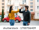 Small photo of Friends greetings with elbows outdoors. Woman and man wearing face mask outdoors. Friends shaking elbows outdoors. Don't shake hands. Elbow greeting style. Young couple greeting with elbows.