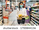 Small photo of Woman with mask safely shopping for groceries amid the coronavirus pandemic in a stocked grocery store.COVID-19 food buying in supermarket.Panic buying,stockpiling.Food shortage.Lockdown preparation.