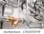 Small photo of Plumbing service. stainless steel pipeline of a heating system in boiler room. Brass coarse filter