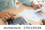 Small photo of The butler is pressing the calculator calculate the various costs that must be paid by the bill. Many invoices held and placed on the table