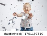 Small photo of A little cute happy girl claps her hands on her first birthday on a white background. Slapstick with confetti. Isolated side view.