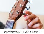 Small photo of Detail of guitar tuned by turning the pegs on the neck. Unrecognizable man explaining step by step instructions to properly tune guitar strings. Music course online concept. Indoor lifestyles.