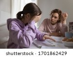 Small photo of Angry adult mother scolding lazy teen daughter for bad school results at home. Frustrated mum talking to upset teenage girl arguing disciplining child must study. Parent and children conflicts concept