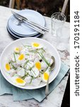Bowl of potato salad topped with hard boiled eggs and chives at a outdoor lunch meal, alfresco dining or at a baebeque - stock photo