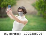 Small photo of A white woman in a fabric face mask while using her phone for selfie and video chats. The new recommendation - everyone to wear masks in public during the coronavirus covid-19 pandemic.