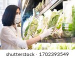Small photo of Asian woman wearing protect face mask and rubber gloves shopping food, fruit and vegetable in grocery department store. Girl choosing celery in supermarket during coronavirus crisis, covid19 outbreak.