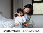 Young Asian Mother Is Reading A ...