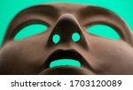 Small photo of Unsettling human mask with empty eyes on a green screen background