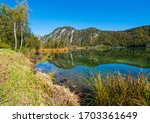 Sunny idyllic colorful autumn alpine view. Peaceful mountain lake with clear transparent water and reflections.  Almsee lake, Upper Austria. - stock photo
