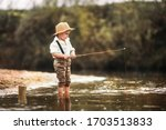 A Fisherman Boy Stands In The...