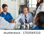 Small photo of Businessman shaking hands with doctor in meeting room. Doctor and representative pharmaceutical shaking hands in medical office. Salesman with new medicines shaking hands in hospital with medical team