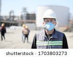 Small photo of The worker (staff, engineer) protects himself from covid-19 (coronavirus) with a protective mask in the construction site.