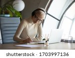 Small photo of Serious female employee in headphones make notes summarize watching webinar on laptop at home, concentrated woman worker brainstorm online with colleague talk on video call or webcam on computer