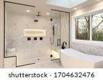 Small photo of Detailes of the larhe walk in shower with white marble and mosaic, light. Three handles, shower head in dark brass.and free standing modern tub.
