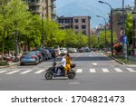 Small photo of Tonglu, Zhejiang Province, China - April 14, 2017 - A young Chinese couple ride on a motor scooter without helmets. The girl wears a yellow dress and rides pillion sitting side saddle.