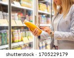 Small photo of Woman reading ingredients information on juice bottle's etiquette