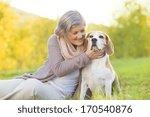 Stock photo senior woman hugs her beagle dog in countryside 170540876