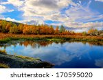Stock photo lake in autumn forest under swimming by clouds 170595020